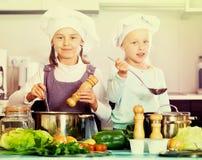 烹调蔬菜汤的两个快乐的愉快的女孩 免版税库存图片