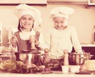 烹调蔬菜汤的两个快乐的愉快的女孩 图库摄影