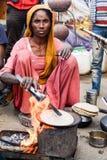 烹调薄煎饼的农村妇女 免版税图库摄影