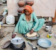 烹调薄煎饼的农村妇女 免版税库存图片