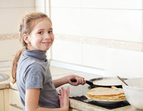 烹调薄煎饼的女孩 免版税图库摄影