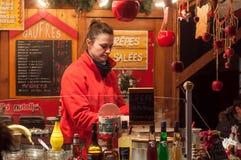 烹调薄煎饼的妇女在圣诞节市场上 免版税库存照片