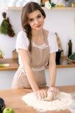 烹调薄饼或手工制造面团的年轻深色的妇女在厨房里 准备在木桌上的主妇面团 库存照片