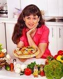 烹调薄饼的愉快的妇女。 免版税库存图片