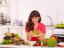 烹调薄饼的愉快的妇女 免版税库存图片