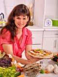 烹调薄饼的愉快的妇女 库存图片