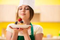 烹调蛋糕的年轻厨师在厨房里 免版税库存图片