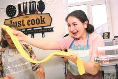 烹调过去的青少年的孩子在大厨房里 免版税库存图片