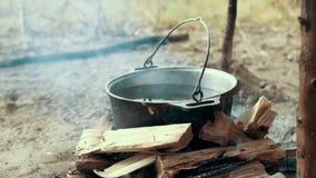 烹调远足在旅游罐的食物在篝火 处理准备的野营的食物 股票录像