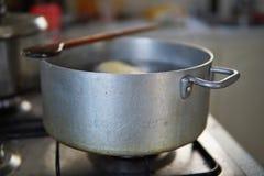 烹调阶段在开水集合的饺子在煤气灶的年迈的银色铝罐 库存图片