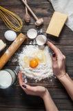 烹调面团用鸡蛋、黄油和牛奶的女性面包师 库存照片