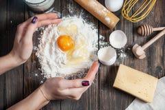 烹调面团用鸡蛋、黄油和牛奶的女性面包师 免版税库存照片