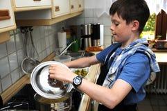 烹调面团的男孩装载面粉 免版税图库摄影