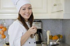 烹调面团的逗人喜爱的女性厨师 免版税图库摄影