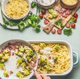 烹调面团砂锅用烤romanesco圆白菜和火腿的妇女女性手在乳脂状的调味汁在厨房用桌背景与 图库摄影