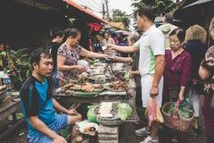 烹调食物和出售的一名地方老挝小山部落妇女在每日早晨市场上在琅勃拉邦, 11月的13日老挝, 2 库存图片