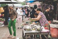 烹调食物和出售的一名地方老挝小山部落妇女在每日早晨市场上在琅勃拉邦, 11月的13日老挝, 2 免版税库存图片