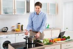 烹调食物的人在厨房里 免版税库存图片