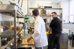 烹调食物的厨师和厨师在餐馆厨房 免版税库存照片