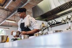 烹调食物的厨师在一个商业厨房里 免版税库存照片