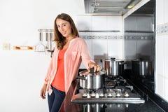 烹调食物的妇女在国内厨房里 库存图片