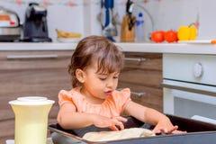 烹调食物的小女孩在厨房里 免版税库存照片