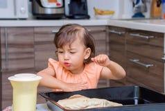 烹调食物的小女孩在厨房里 库存图片