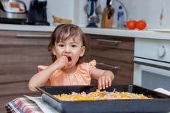 烹调食物的小女孩在厨房里 免版税库存图片
