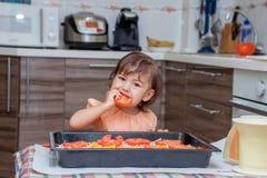 烹调食物的小女孩在厨房里 库存照片