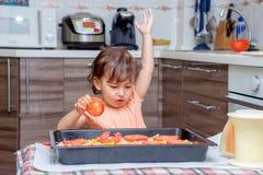烹调食物的小女孩在厨房里 免版税图库摄影