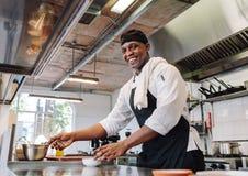 烹调食物的微笑的厨师在餐馆厨房 免版税库存图片