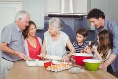 烹调食物的愉快的家庭在厨房里 免版税库存照片