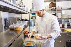 烹调食物的愉快的男性厨师在餐馆厨房 免版税库存照片