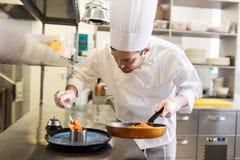 烹调食物的愉快的男性厨师在餐馆厨房 库存图片