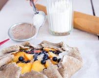 烹调饼干用桃子和蓝莓,倒糖 库存照片