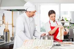 烹调馄饨面团的厨师在厨房里 图库摄影