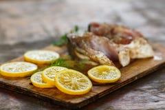 烹调鱼、一块新未加工的鲜美在木板的鱼与柠檬切片的和荷兰芹的过程 库存图片