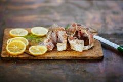 烹调鱼、两块新未加工的鲜美在木板的鱼与柠檬切片的和荷兰芹的过程 库存照片