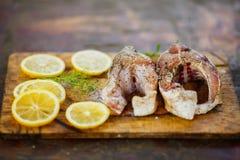 烹调鱼、两块新未加工的鲜美在木板的鱼与柠檬切片的和荷兰芹的过程 图库摄影