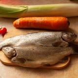 烹调鱼晚餐 未加工的鲈鱼平位置与菜的在土气背景,顶视图 库存图片