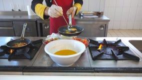 烹调鲜美蔬菜菜肴的无法认出的厨师在餐馆现代厨房里  增加在平底锅的男性厨师成份 股票视频