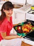 烹调鸡的妇女在厨房。 免版税库存图片