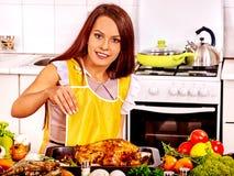 烹调鸡的妇女在厨房 免版税库存图片
