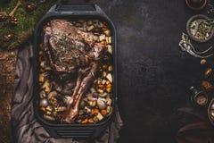 烹调鹿肉鹿的烘烤腿的准备与骨头的在有食道菜的生铁平底锅在黑暗的厨房用桌背景 免版税库存照片