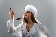 烹调,吃,研究 有一个杓子的女孩在烹调帽子 免版税库存照片