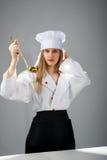 烹调,吃,研究 有一个杓子的女孩在烹调帽子 免版税库存图片