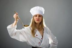 烹调,吃,研究 有一个杓子的女孩在烹调帽子 库存照片