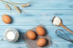 烹调,牛奶、鸡蛋、小麦面粉和厨具的成份在蓝色木背景,顶视图 免版税库存图片