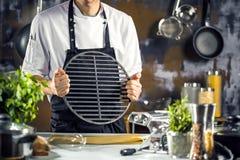 烹调,行业和人概念-做食物的男性厨师厨师在餐馆厨房 免版税图库摄影