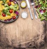 烹调素食面团用沙拉和菜,油和盐食物装置边界的,在木土气后面安置文本 免版税库存图片